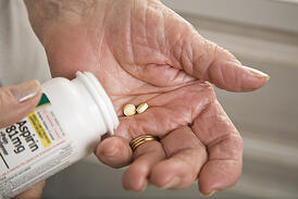 Elderly woman taking aspirin