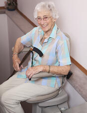 Elderly woman carrying a cane while riding a stair lift