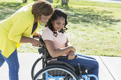Woman pushing a disabled teen in a wheelchair and chatting with her