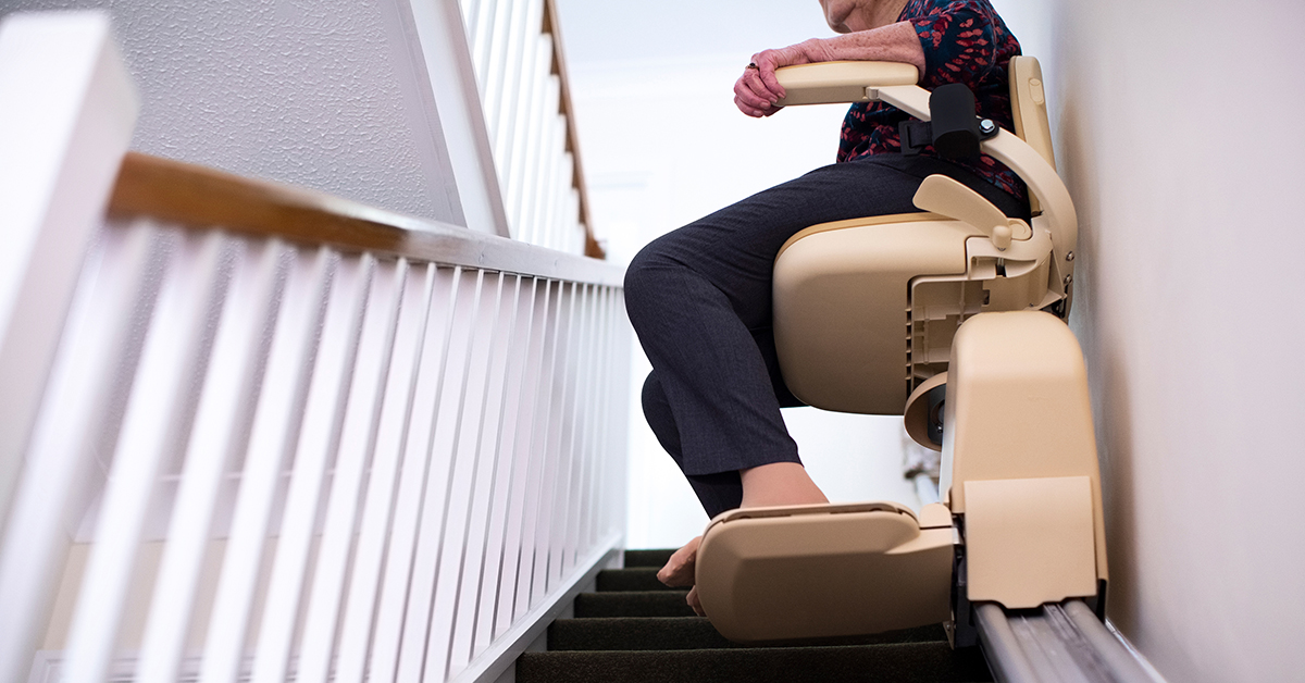 Elderly woman riding a stair lift in her home