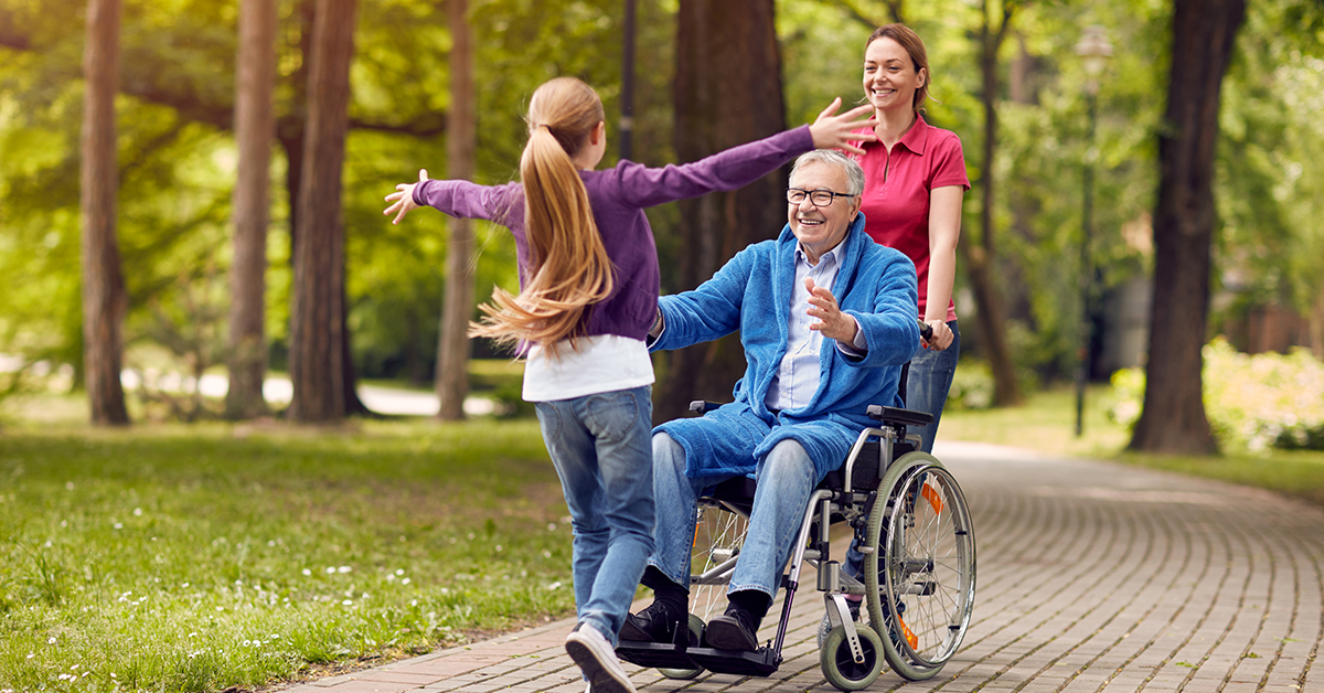 Grandfather in a wheelchair with his daughter and granddaughter