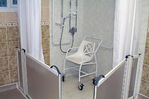 Accessible roll-in shower with a seat and handheld shower head