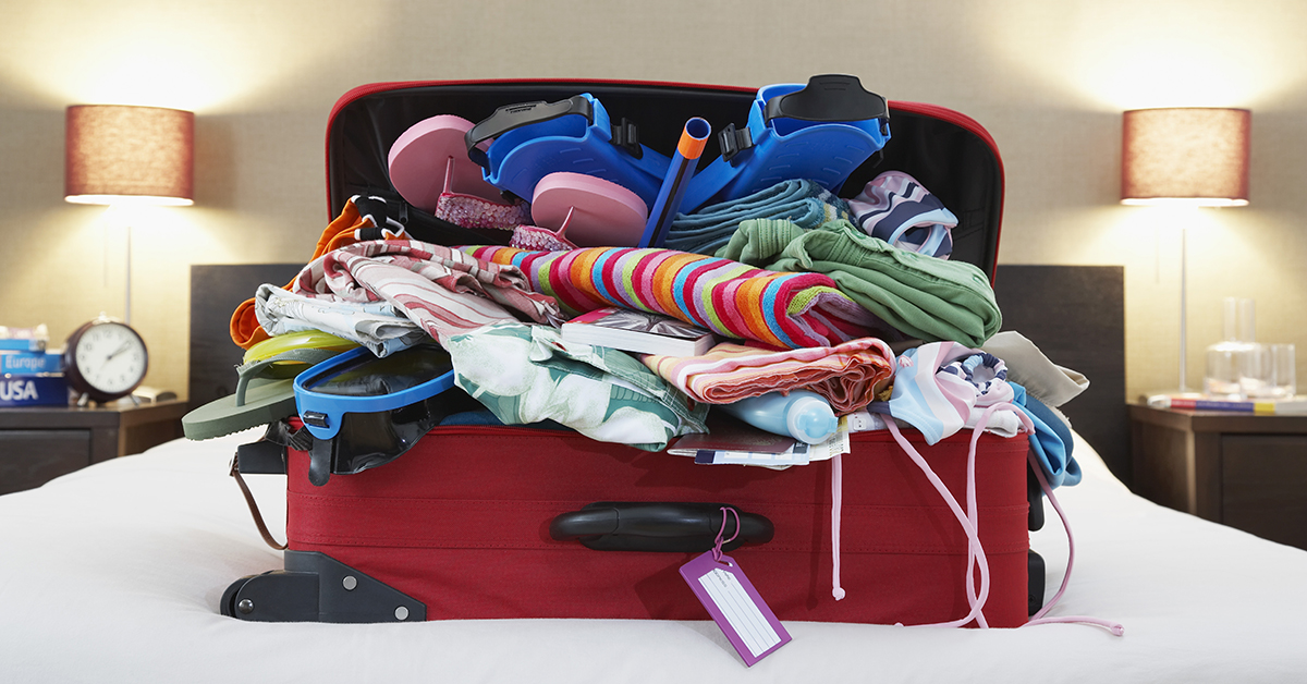 Overstuffed luggage on a bed