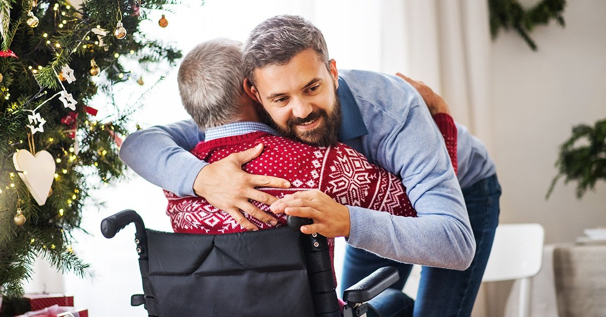 Man hugging father in wheelchair