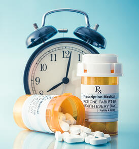 Medication bottles and an alarm clock