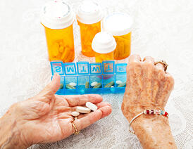 Elderly woman using an organizing pill dispenser