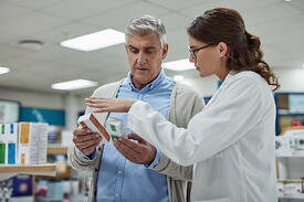 Pharmacist discussing medication with senior