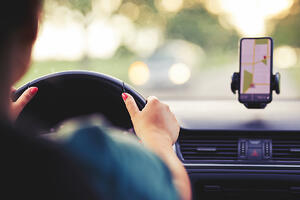 Woman driving and using smartphone's GPS