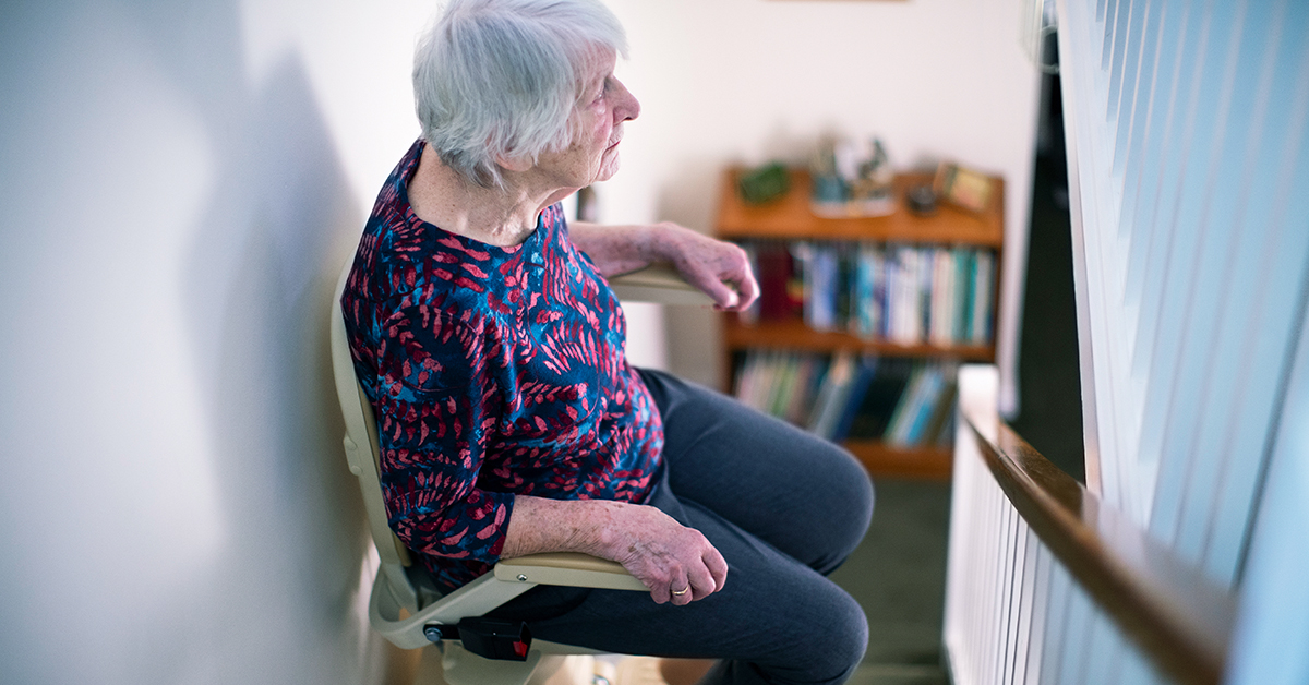 Eldery woman riding a stair lift in her home