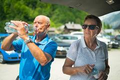 Senior couple on road trip taking a water break